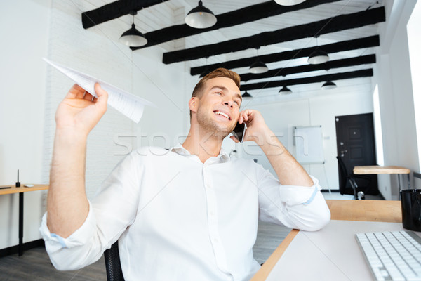Cheerful businessman talking on cell phone and throwing paper plane Stock photo © deandrobot