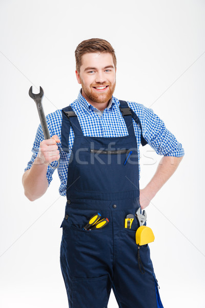 Cheerful attractive young worker in overall holding wrench Stock photo © deandrobot