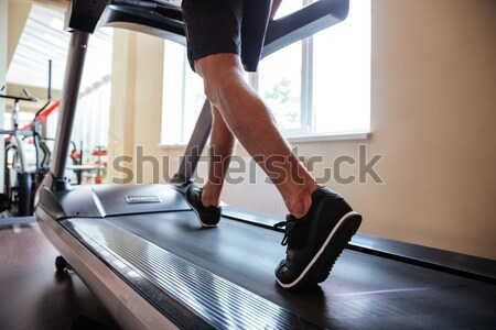 Legs of young man athlete running on treadmill in gym Stock photo © deandrobot