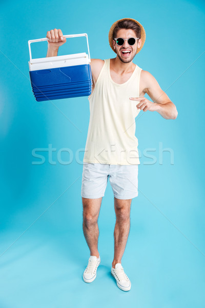 Happy young man holding and pointing on cooler bag Stock photo © deandrobot