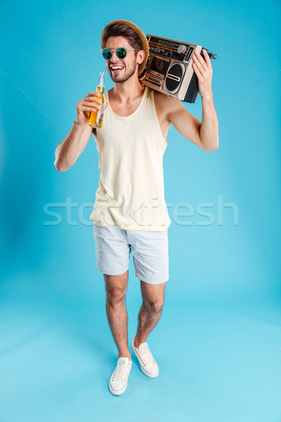 Cheerful young man with boombox walking and drinking beer Stock photo © deandrobot