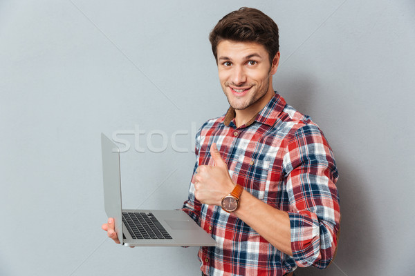 Cheerful young man holding laptop and showing thumbs up Stock photo © deandrobot