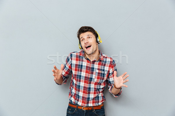 Happy young man in headphones listening to music and singing Stock photo © deandrobot