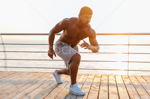 Shirtless african man athlete warming up and training on pier Stock photo © deandrobot