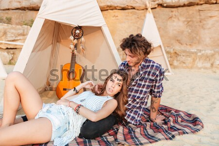 Couple lying and looking away near teepee on the beach Stock photo © deandrobot