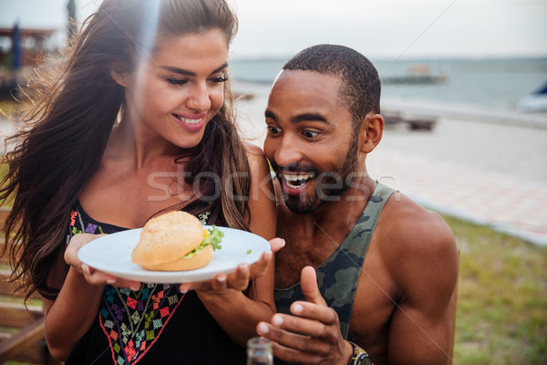 Young man hungry looking at the burger on a plate Stock photo © deandrobot