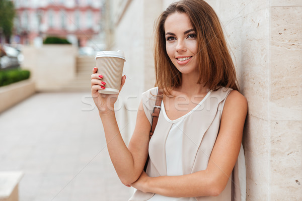 Happy woman holding take away coffee and looking at camera Stock photo © deandrobot