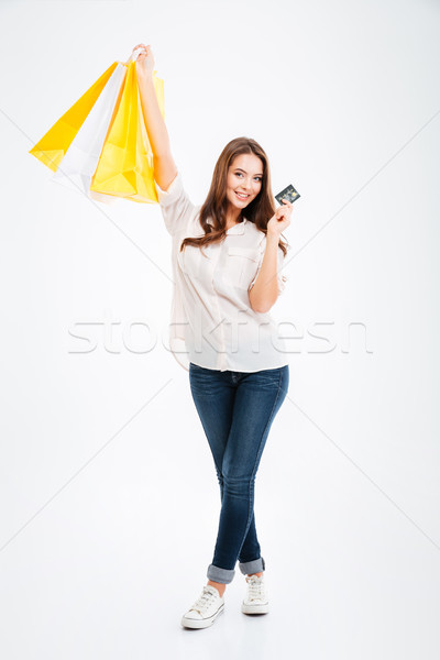Pretty young woman holding shopping bags and bank card Stock photo © deandrobot