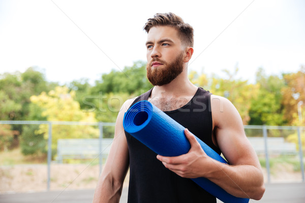 Concentrated serious male yoga instructor holding mat Stock photo © deandrobot