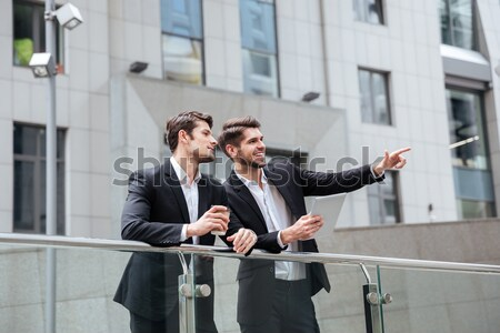 Two businessmen talking and drinking coffee in the city Stock photo © deandrobot