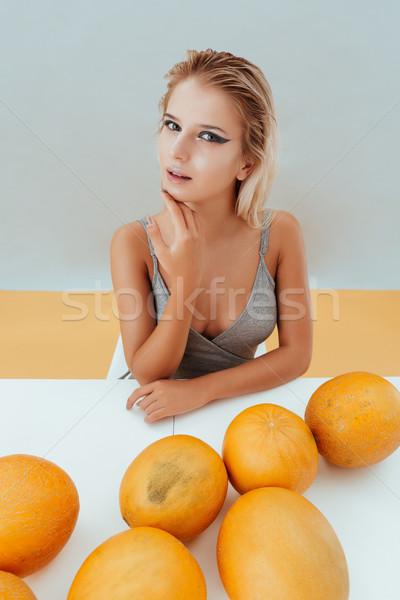 Gyönyörű fiatal nő ül asztal szürke citromsárga Stock fotó © deandrobot