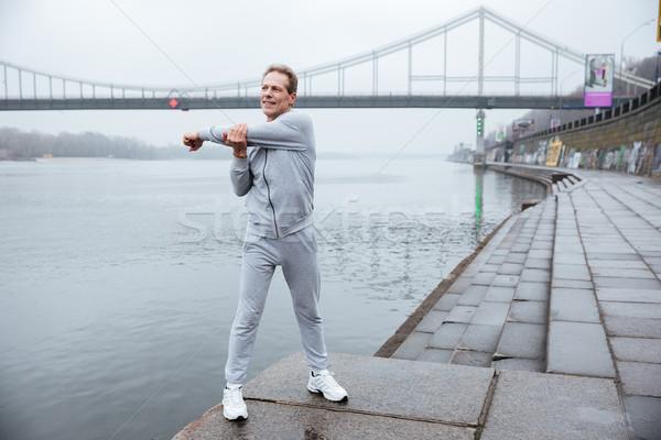 Full length runner warming up near the river Stock photo © deandrobot
