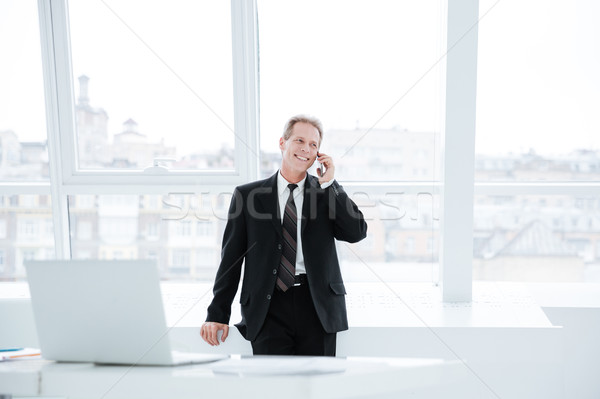 Elderly business man talking at phone near the table Stock photo © deandrobot