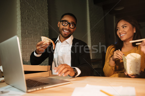 Two colleagues working at night while eating pizza. Stock photo © deandrobot