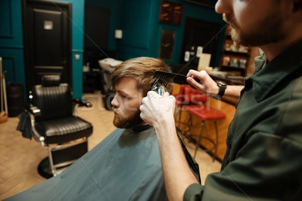 Jeunes barbu homme salon de coiffure électriques Photo stock © deandrobot