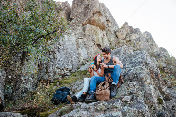 Portrait of a happy couple resting while hiking in mountains Stock photo © deandrobot