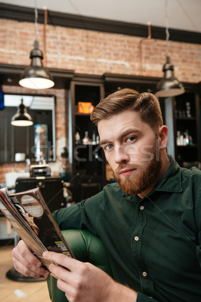 Young man sitting in barbershop and reading magazine Stock photo © deandrobot