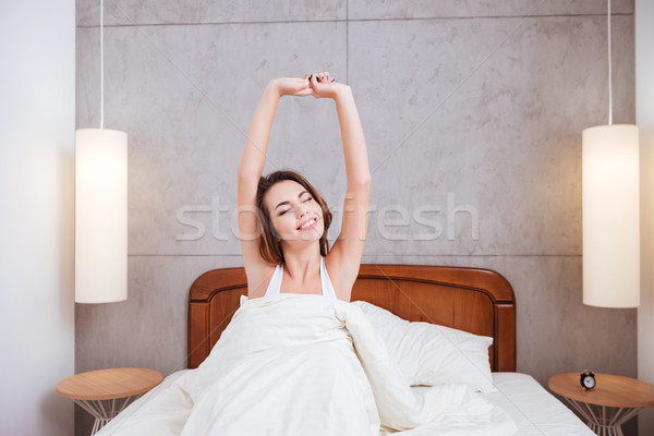 Lovely young woman waking up and stretching in bed Stock photo © deandrobot