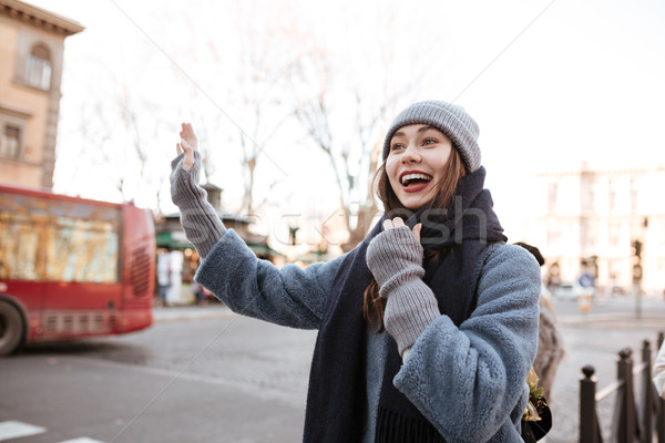 Happy woman trying to stop a taxi on the street Stock photo © deandrobot