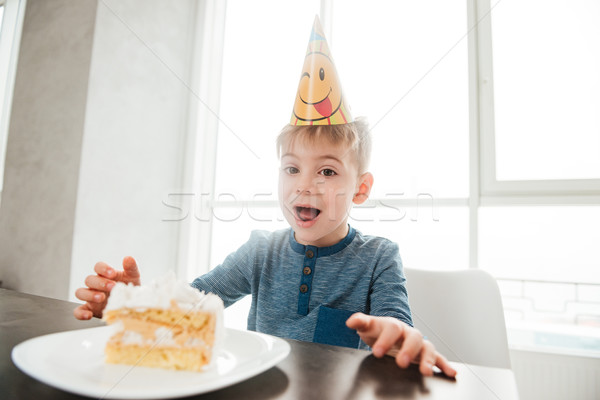 Happy birthday boy sitting in kitchen near cake and eating. Stock photo © deandrobot