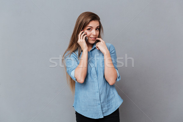 Shy Woman in shirt talking on phone Stock photo © deandrobot