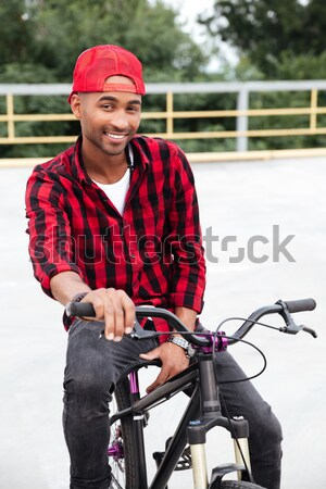 Cheerful dark skinned guy wearing cap sitting on his bicycle Stock photo © deandrobot