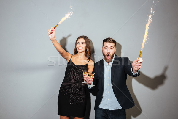 Happy cheerful couple celebrating holding glasses with champagne and petards Stock photo © deandrobot