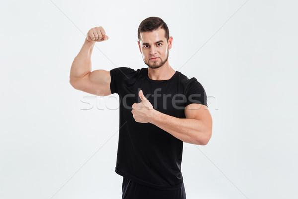 Bodybuilder biceps regarder caméra isolé Photo stock © deandrobot