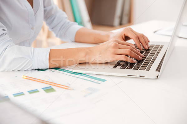 Cropped photo of businesswoman using laptop. Stock photo © deandrobot