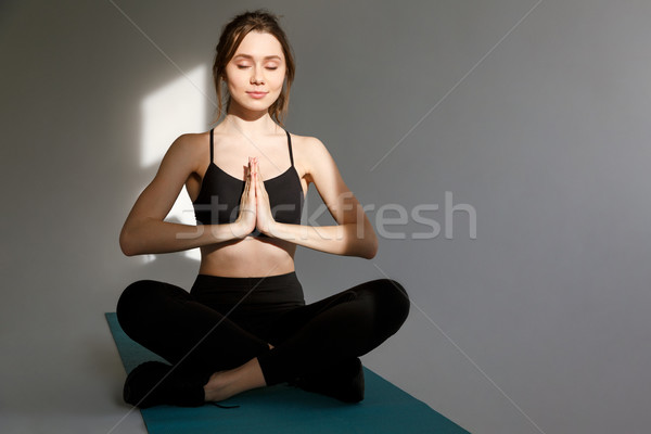 Young woman doing yoga meditation in lotus pose on mat Stock photo © deandrobot