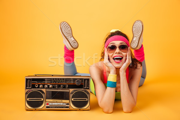 Cheerful beautiful young sportswoman with boombox lying and having fun Stock photo © deandrobot