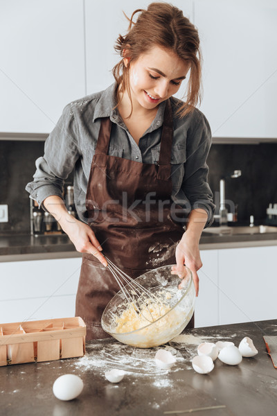 Beautiful woman cooking the dough. Looking aside. Stock photo © deandrobot