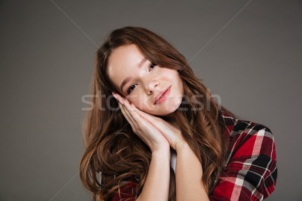 Lovely woman in plaid shirt standing and showing sleeping gesture Stock photo © deandrobot