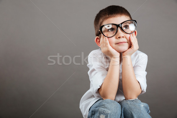 Thoughtful little boy in glasses sitting and thinking Stock photo © deandrobot