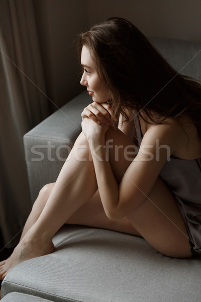 Vertical image of woman in nightie sitting on sofa Stock photo © deandrobot