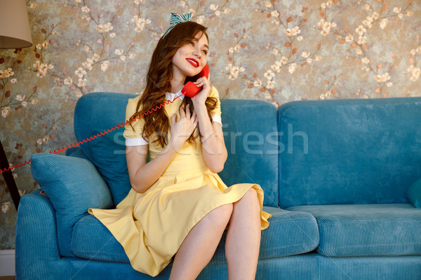 Happy young pin-up lady talking by phone. Stock photo © deandrobot
