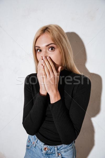 Surprised young woman covering mouth with hands Stock photo © deandrobot