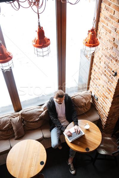 Verticale immagine barbuto utilizzando il computer portatile cafe Foto d'archivio © deandrobot