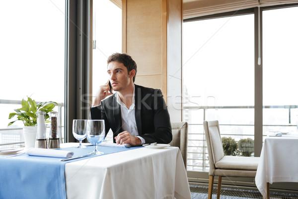Calm Man in restaurant talking on phone Stock photo © deandrobot