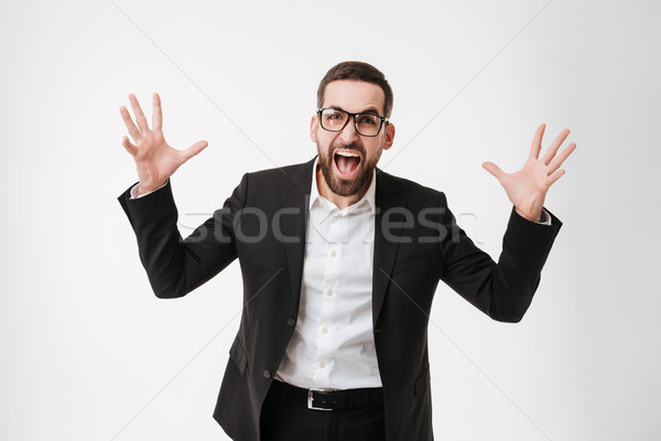 Emotional young bearded businessman Stock photo © deandrobot