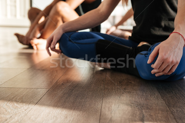 Woman sitting and practicing yoga in group at studio Stock photo © deandrobot
