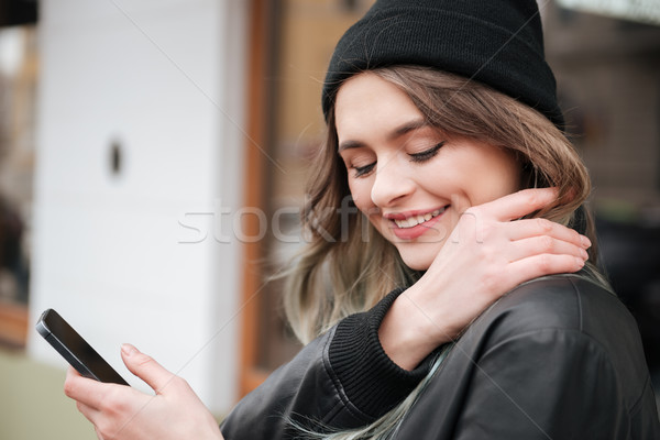 Pretty woman wearing hat walking on the street while chatting Stock photo © deandrobot