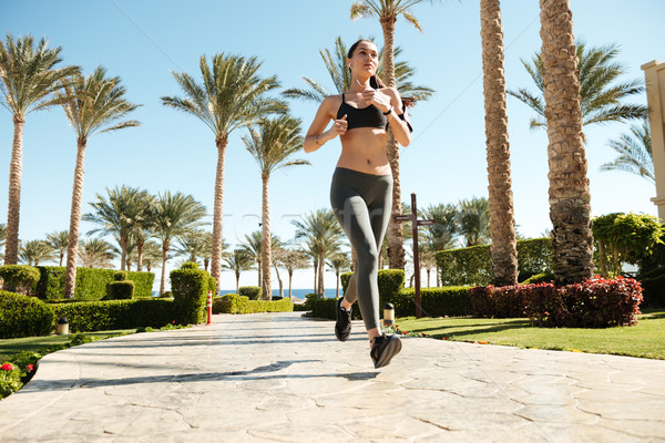 Beautiful young woman athlete running on summer resort Stock photo © deandrobot