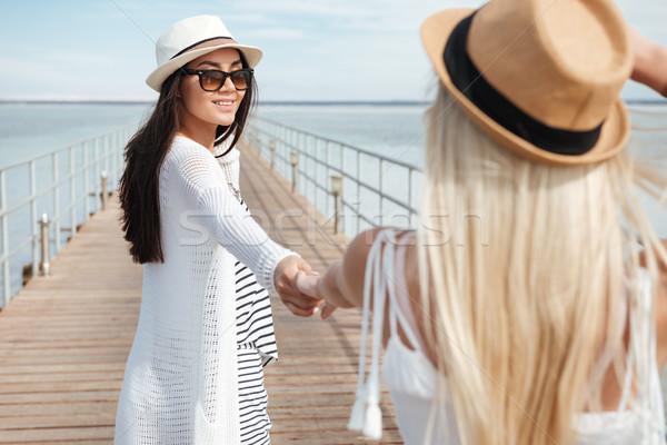 Twee gelukkig jonge vrouwen holding handen lopen pier Stockfoto © deandrobot