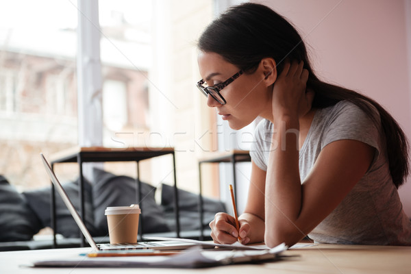 Pretty young caucasian woman using laptop computer and writing notes. Stock photo © deandrobot