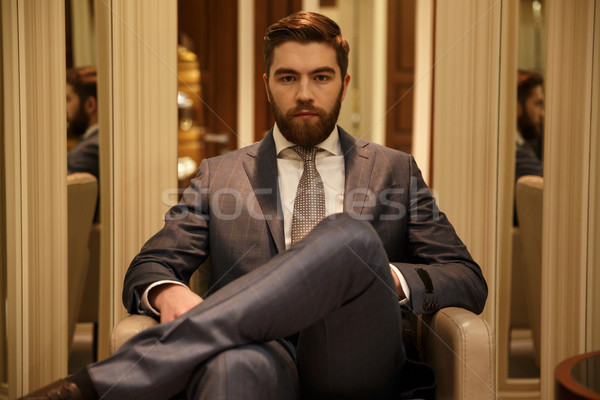 Serious man sitting on armchair in shop Stock photo © deandrobot