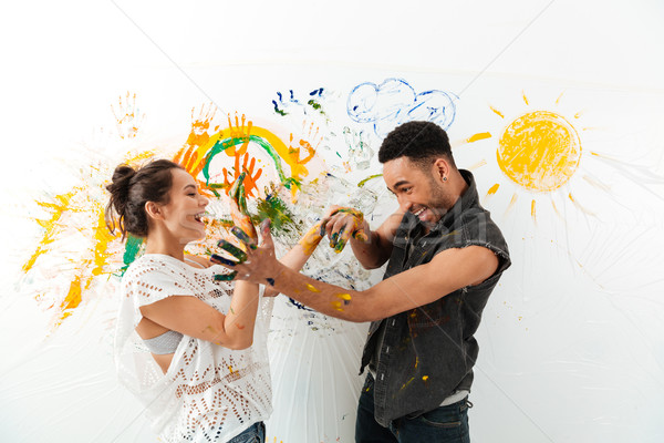 Couple with hands dirty in paints laughing and having fun Stock photo © deandrobot