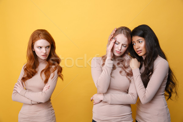 Angry redhead lady looking at african woman calms blonde woman Stock photo © deandrobot