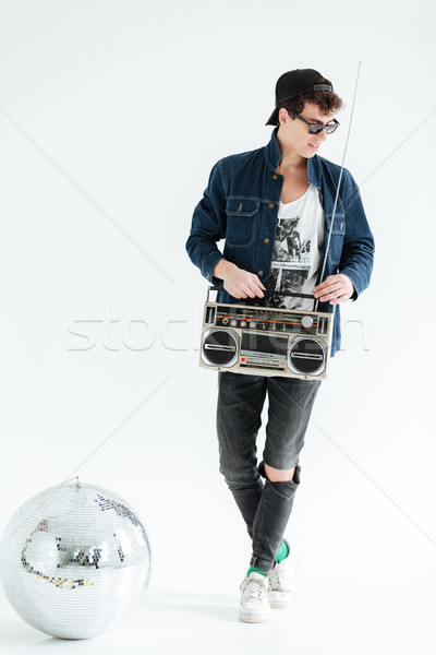 Cheerful young man holding boombox near disco ball. Stock photo © deandrobot