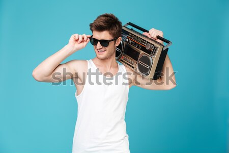 Handsome young man holding boombox Stock photo © deandrobot